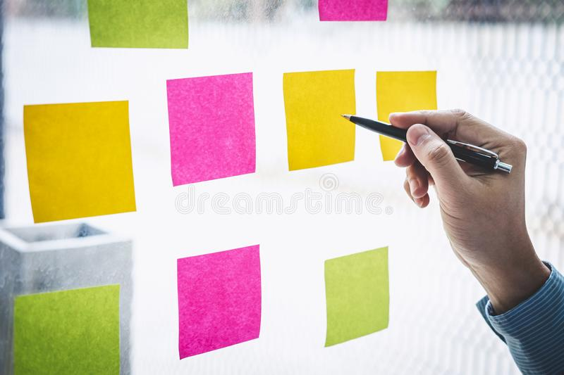 Businessman use post it notes to planning idea and business marketing strategy, Sticky note on glass wall royalty free stock image