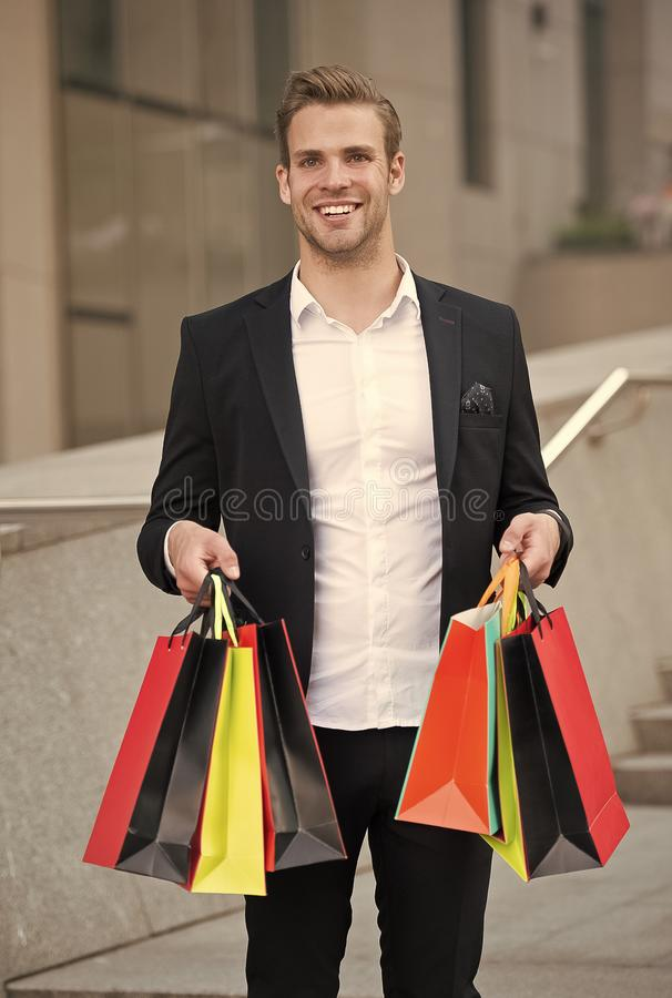 Businessman use shopping application. Man carries shopping bags urban background. Successful businessman shopping online stock photography