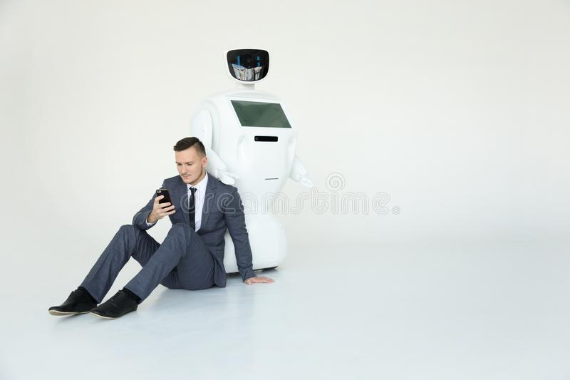 Businessman uses a smartphone while sitting on the floor next to a robot. Modern Robotic Technologies. Humanoid. A robot with human face and body - humanoid stock image