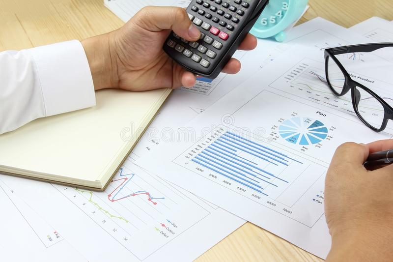 Businessman using calculator with business graph stock images
