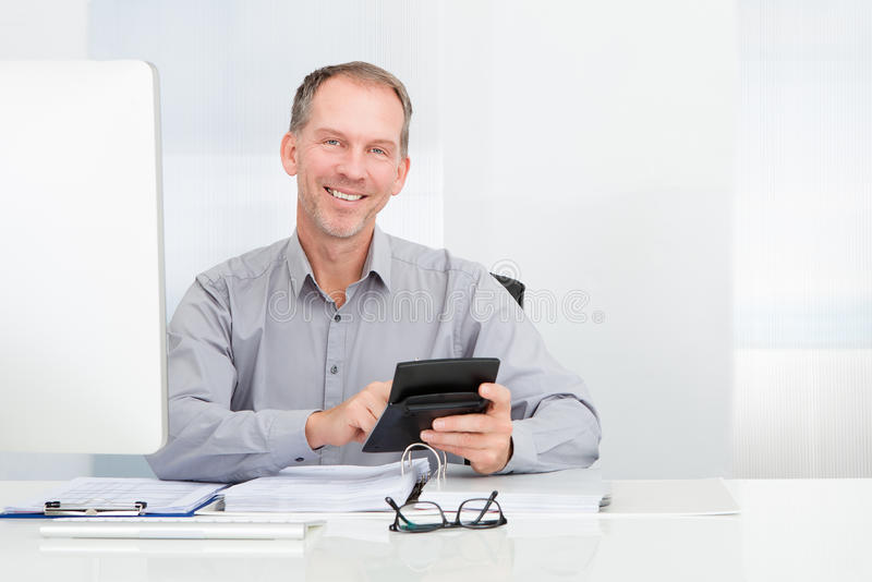 Businessman using calculator. Happy Businessman Sitting In Front Of Computer Holding Calculator stock image