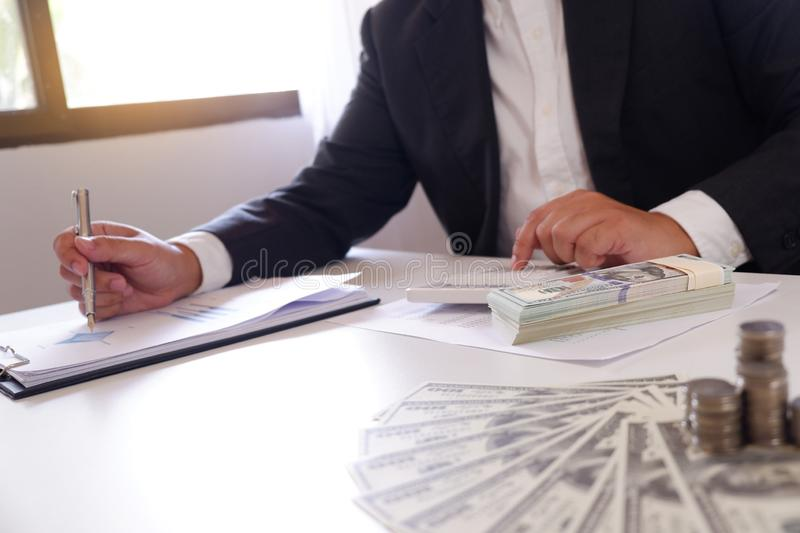 Businessman using calculator with money and stack of coins on the desk stock images