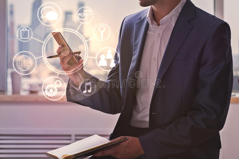 Businessman using cellphone with business diagram. Attractive young businessman using cellphone with circular business diagram at workplace. Communication stock image