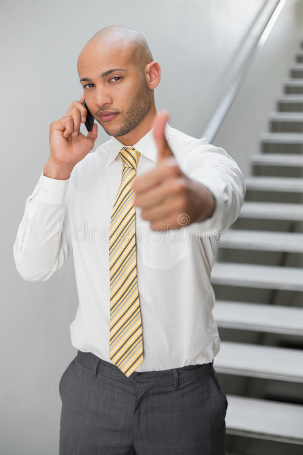 Businessman using cellphone and gesturing thumbs up royalty free stock photography