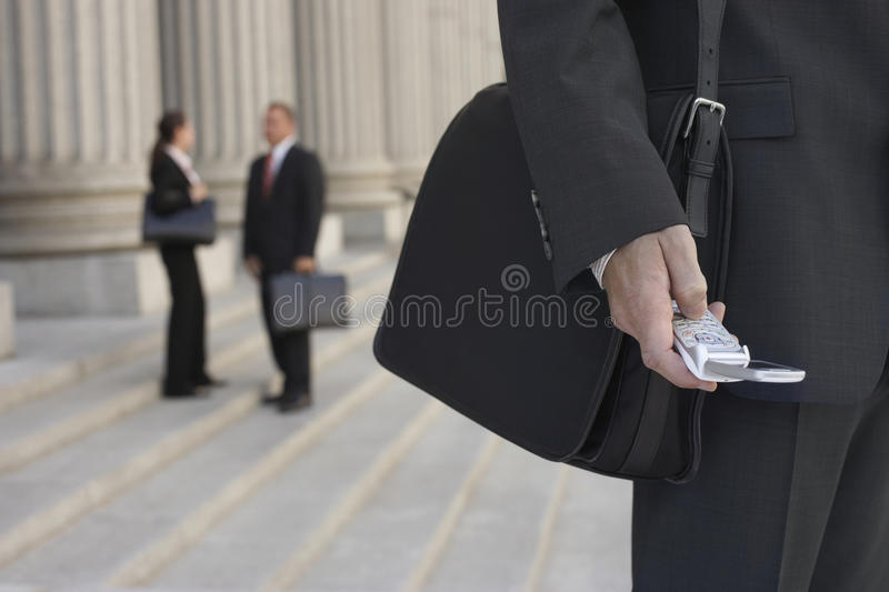 Businessman Using Cellphone And People Talking In Background stock image