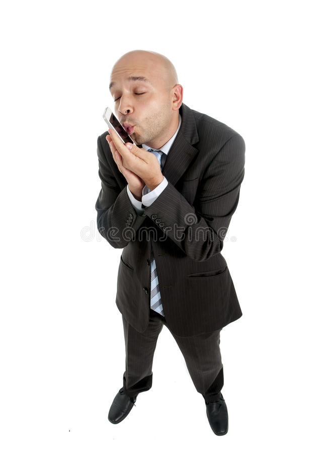 Businessman using compulsively cell phone smiling in mobile addiction concept stock photo