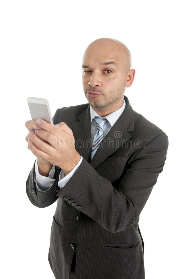 Businessman using compulsively cell phone smiling in mobile addiction concept royalty free stock photography