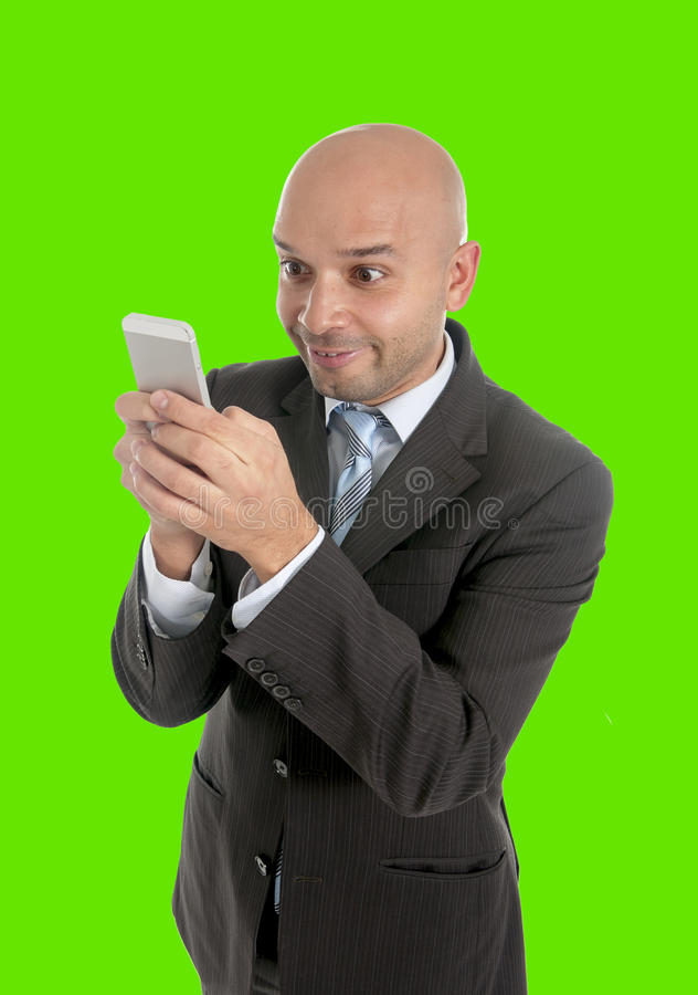 Businessman using compulsively cell phone smiling in mobile addiction green chroma key royalty free stock photography
