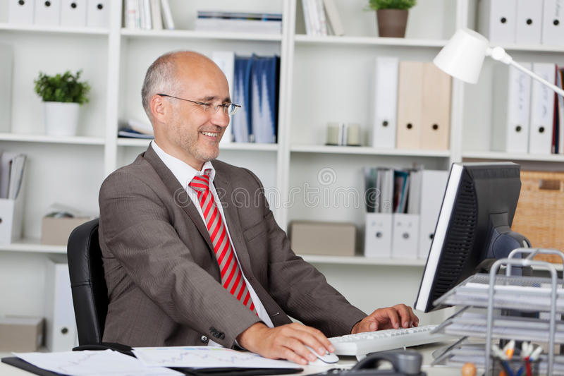 Download Businessman Using Computer At Desk Stock Image - Image: 31196511