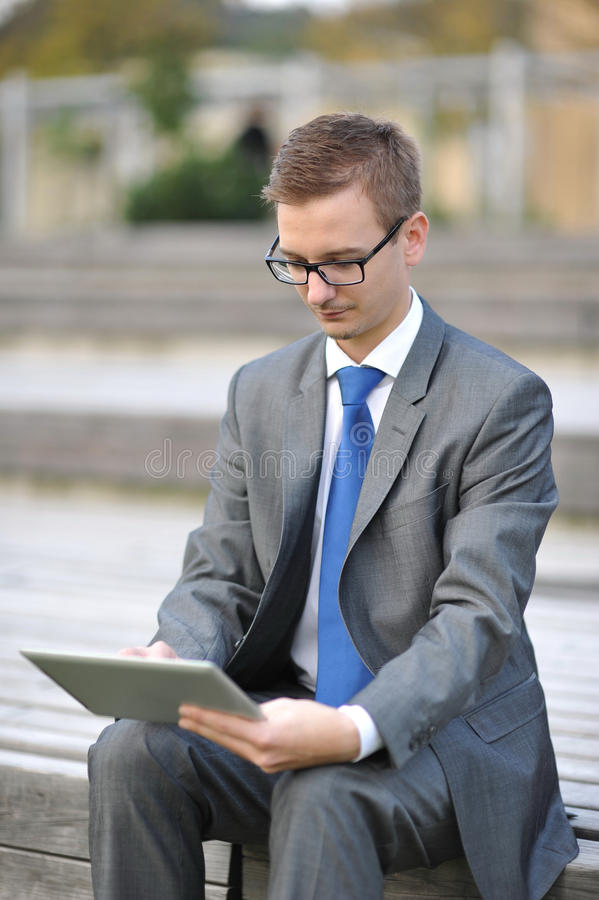 Businessman using computer tablet,. Shoot in the city, late afternoon/early evening. Man is wearing a gray suit and blue tie stock images