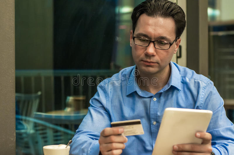 Businessman using a credit card and digital tablet for buying on internet. Businessman using a credit card and digital tablet for buying on-line. Man buying on stock images