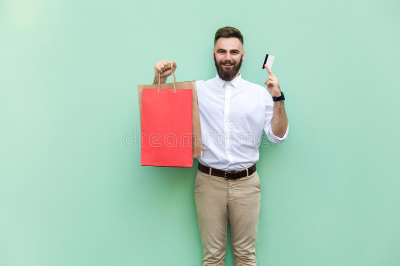 Businessman using credit card for online shopping. Looking at camera and toothy smile. Indoor, studio shot, green background royalty free stock photography