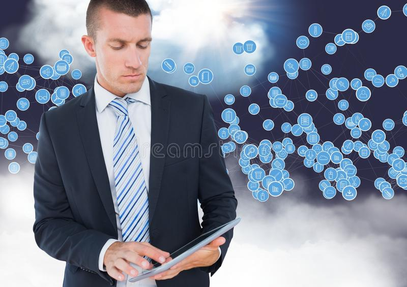 Businessman using digital tablet against technology icons in sky. Digital composition of businessman using digital tablet against technology icons in sky stock image