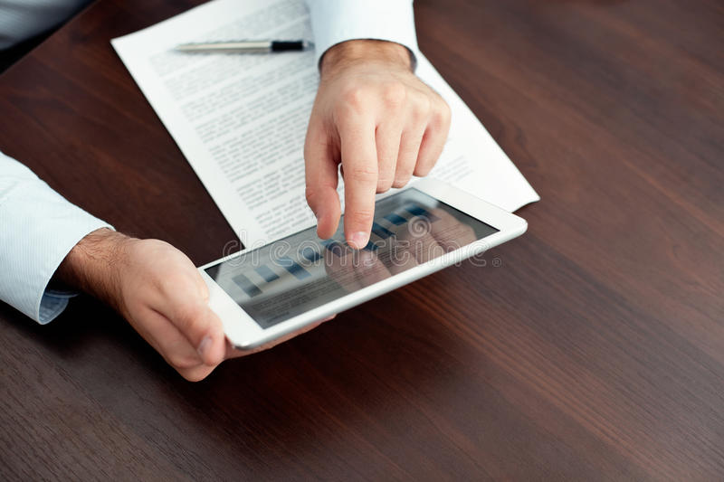 Businessman using digital tablet by the desk royalty free stock photo