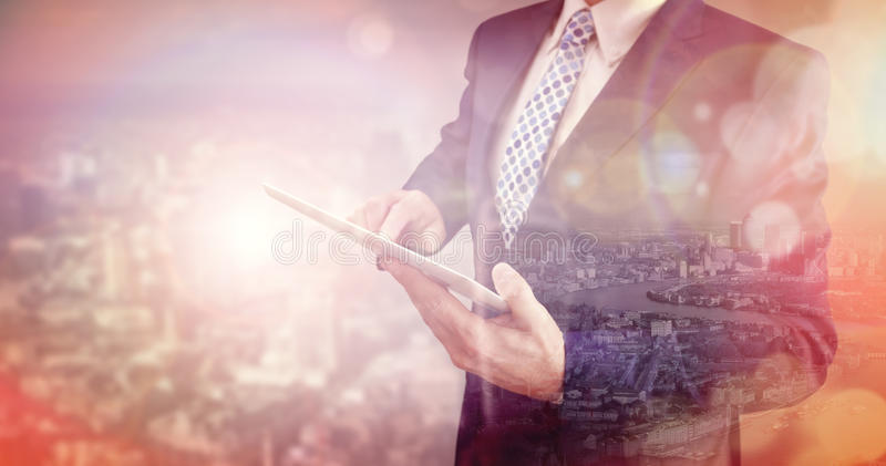 Businessman using digital tablet with double exposure of city stock photo