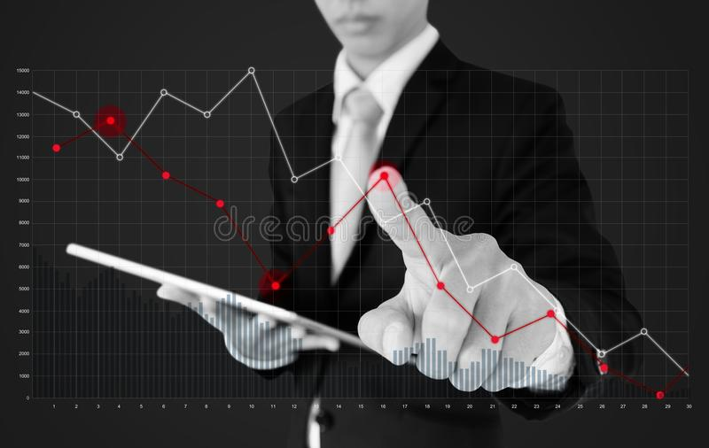 Businessman using digital tablet and pointing finger on falling graph diagram. Business finance and economy crisis stock image