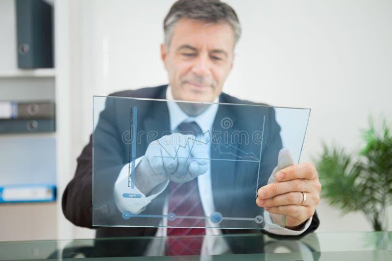 Businessman using futuristic touchscreen to view graph stock photos