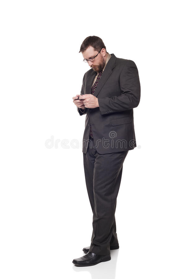 Businessman using a gadget in his hands. Isolated full length studio shot of a businessman looking down at a gadget he is holding in his hands while standing stock images