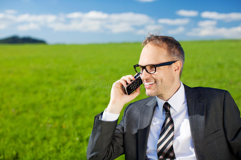 Businessman using his mobile in the countryside royalty free stock images