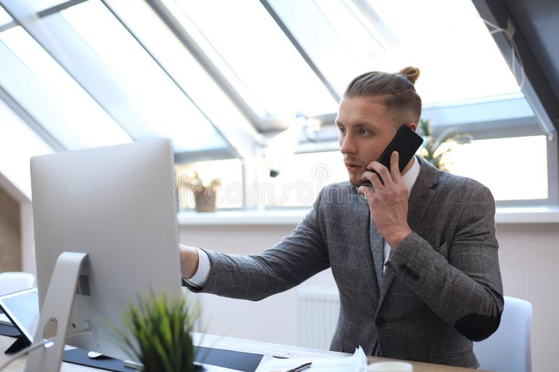 Businessman using his mobile phone in the office.  stock photo