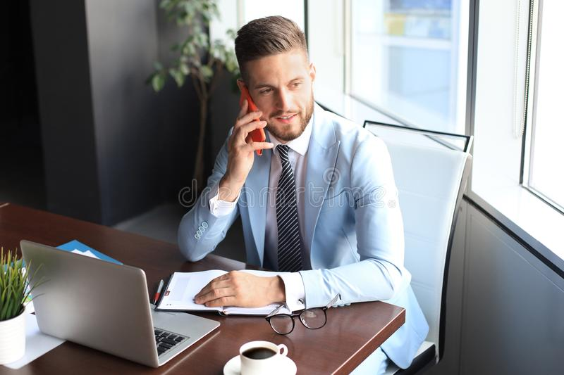 Businessman using his mobile phone in the office. Businessman using his mobile phone in the office royalty free stock images
