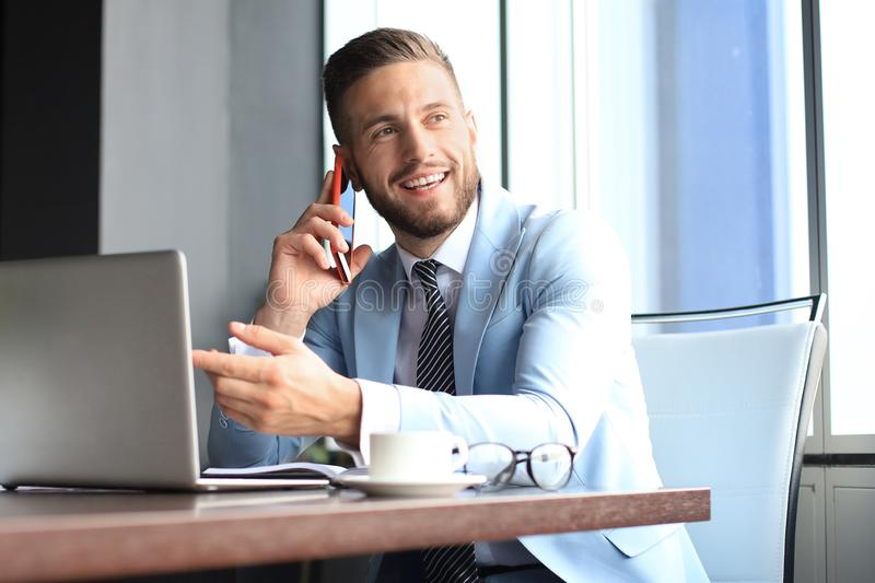 Businessman using his mobile phone in the office. Businessman using his mobile phone in the office stock image