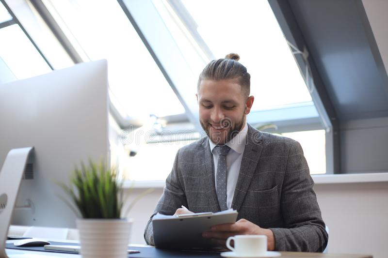 Businessman using his tablet in the office.  stock image