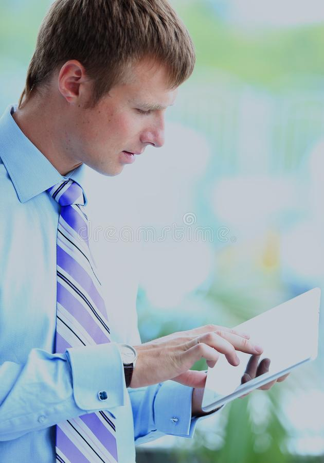 Businessman using his tablet in the office. Businessman using his tablet in the office royalty free stock photo