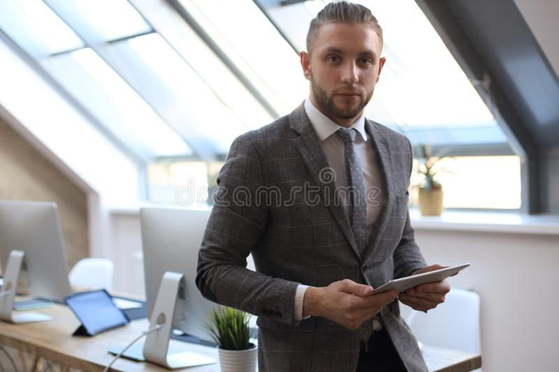 Businessman using his tablet in the office.  stock photography