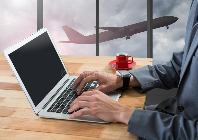 Businessman using laptop in airport with plane at window royalty free stock image