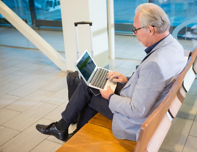 Businessman Using Laptop In Airport Waiting Area royalty free stock image