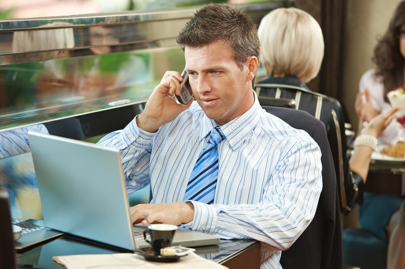 Businessman using laptop in cafe royalty free stock photos