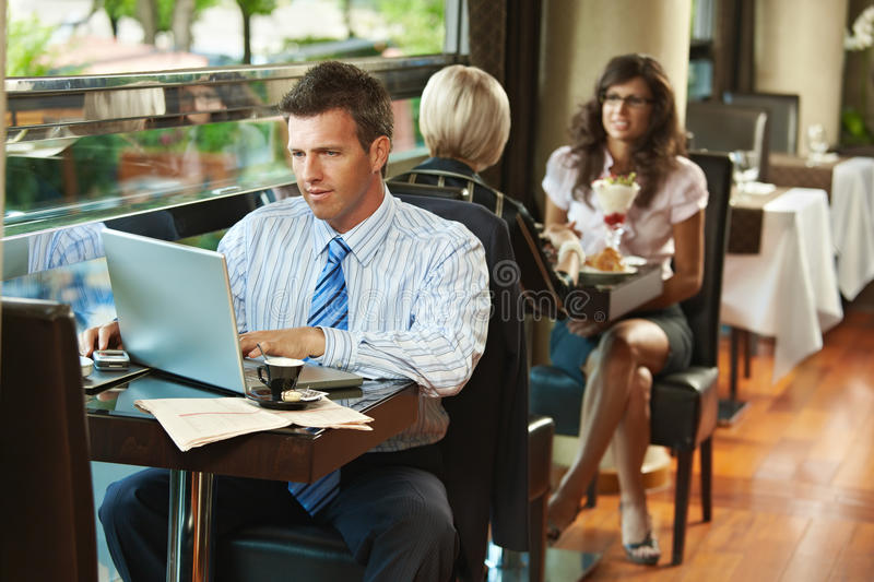 Businessman using laptop in cafe stock images