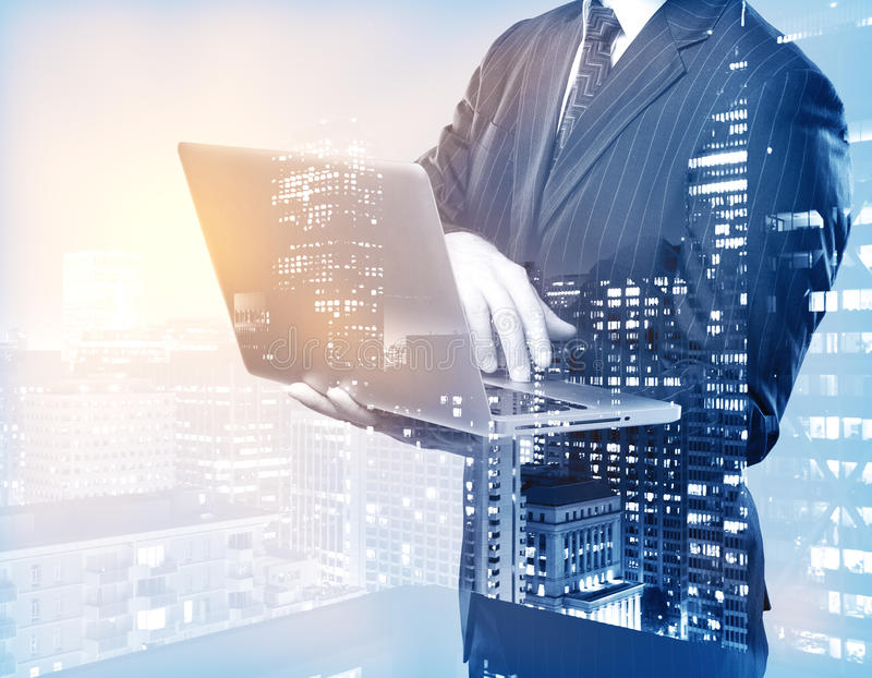 Businessman using laptop. On city background. Double exposure. Communication concept royalty free stock images