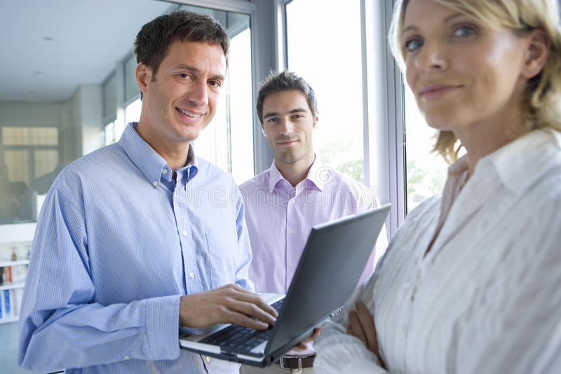 Businessman using laptop computer by colleagues standing by window, smiling, portrait stock images
