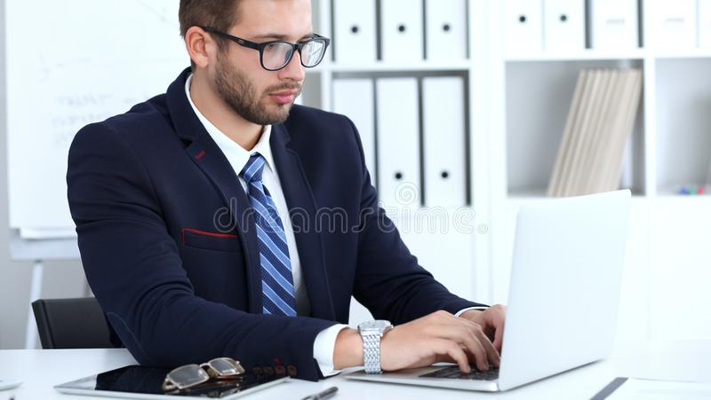 Businessman using laptop computer while sitting at the desk in office. Focus at cheerful smiling bearded man wearing royalty free stock images