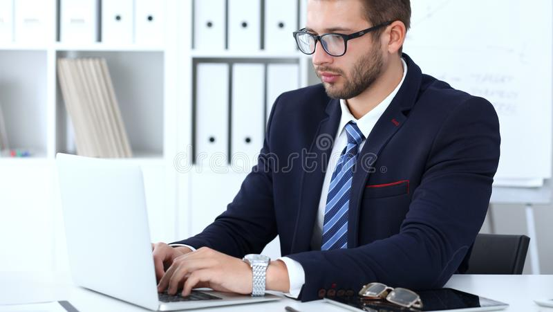 Businessman using laptop computer while sitting at the desk in office. Focus at cheerful smiling bearded man wearing royalty free stock photo