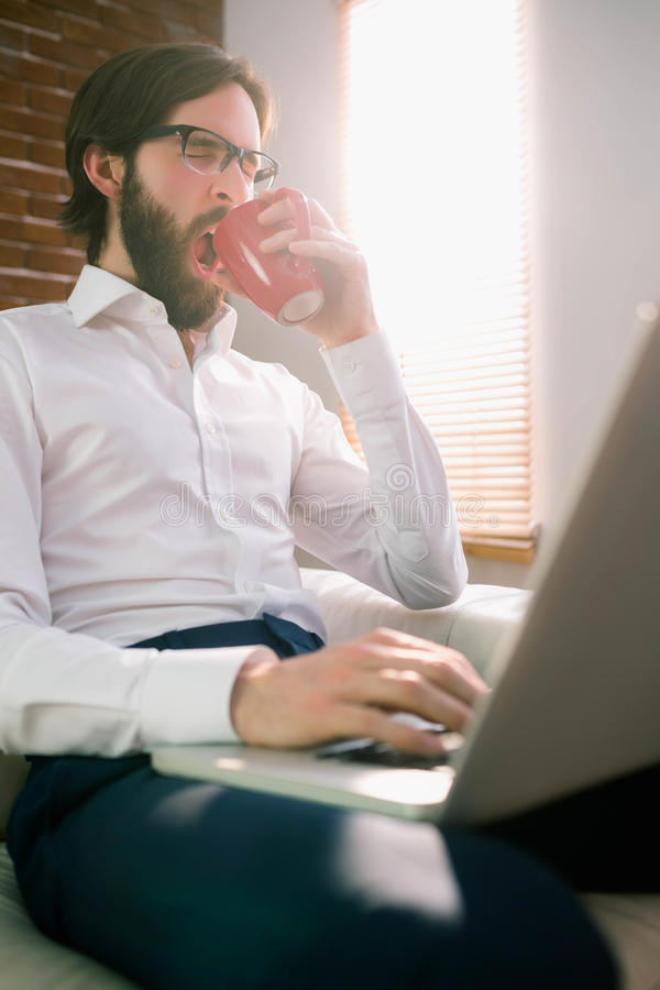 Businessman using laptop on the couch stock images