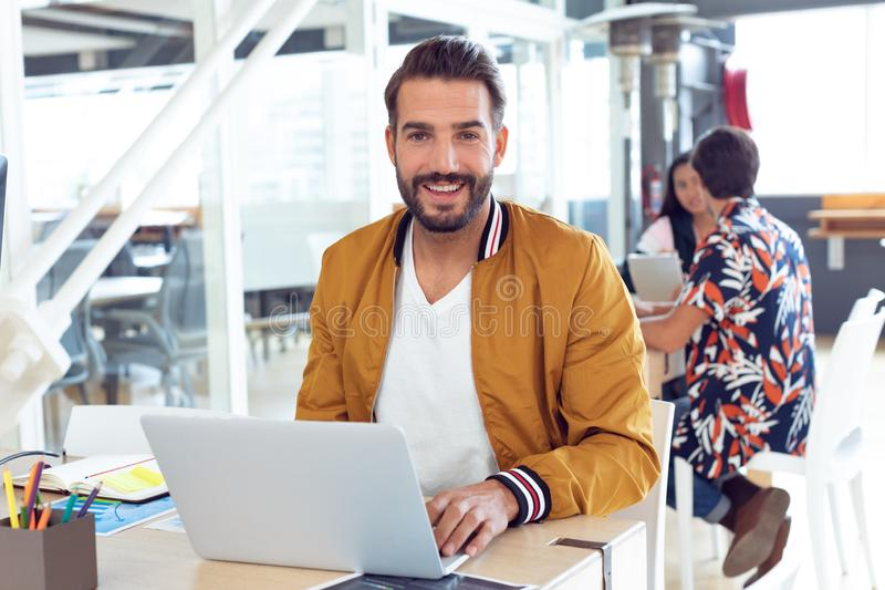Businessman using laptop on desk in the office. Portrait of smiling Caucasian  Businessman using laptop on desk in the office while colleagues speaking together royalty free stock photos