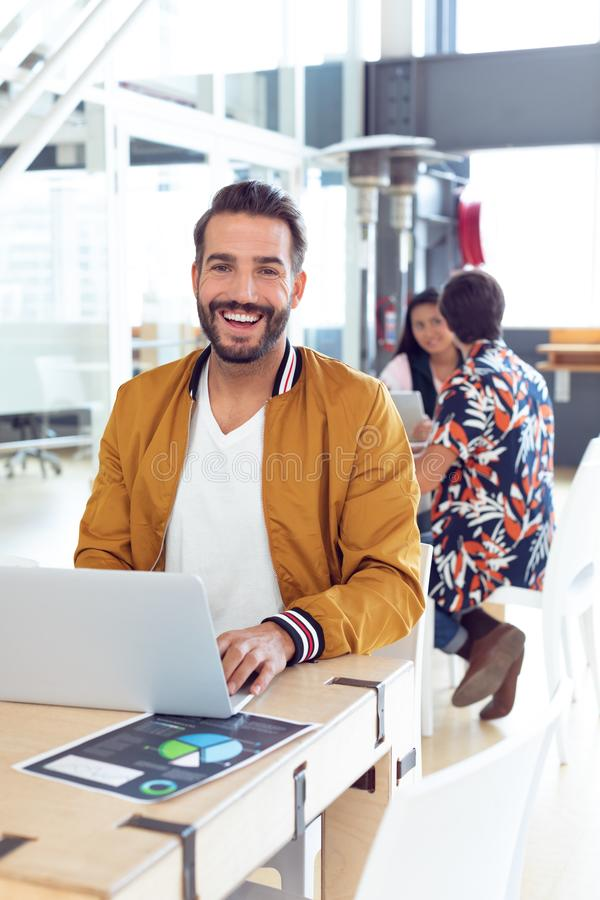 Businessman using laptop on desk in the office. Portrait of smiling Caucasian Businessman using laptop on desk in the office while colleagues speaking together royalty free stock photo