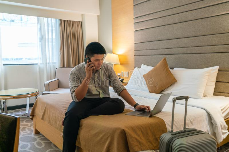 Businessman using a laptop in hotel room stock images