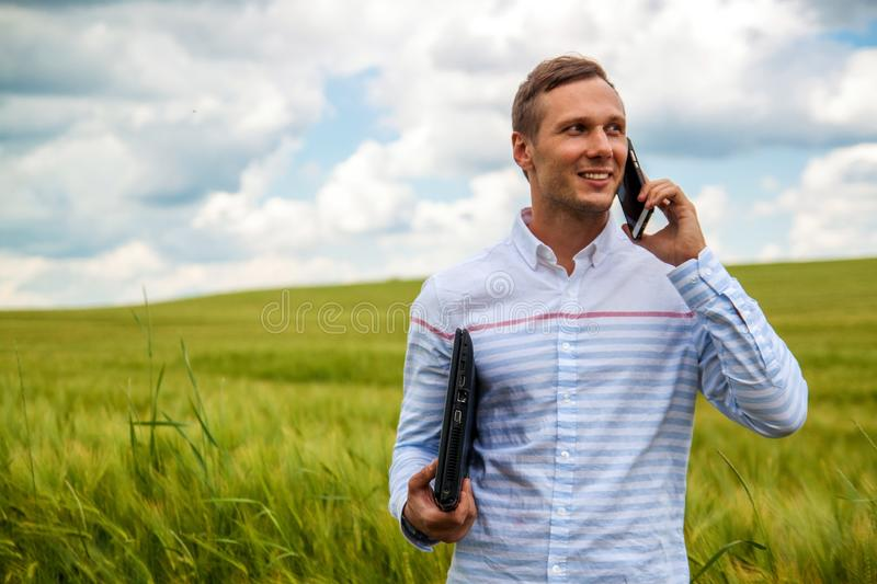 Businessman using laptop and smartphone in wheat field. royalty free stock photography