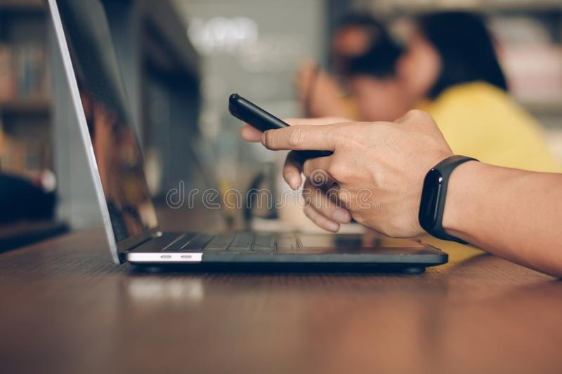 Businessman using laptop and typing on mobile smart phone, business people with technology concept. Close up hand man working. stock image