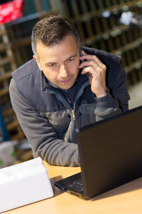 Businessman using laptop in warehouse stock images