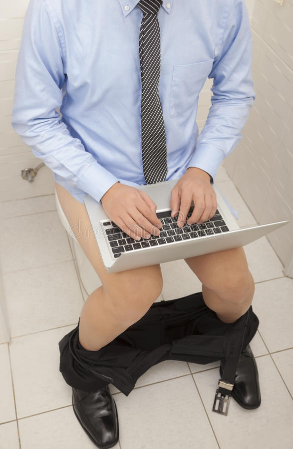 Businessman Using Laptop Working  In Toilet Stock Photography