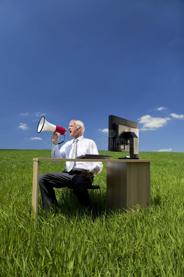 Businessman Using Megaphone In A Field