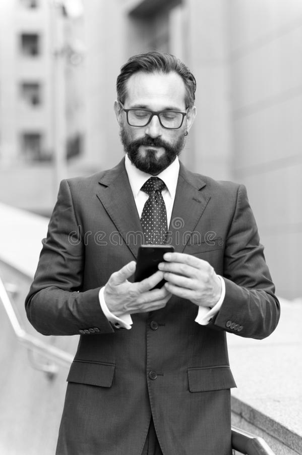 Businessman using mobile app texting outside of office in urban city with skyscrapers buildings in background. Caucasian bearded. Businessman using mobile app stock image