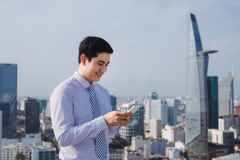 Businessman using mobile phone app texting outside of office in urban city with skyscrapers buildings in the background royalty free stock images