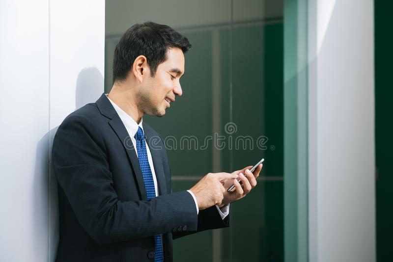 Businessman using mobile phone app texting outside of office in urban city with skyscrapers buildings in the background. Young asian man holding smartphone for royalty free stock image