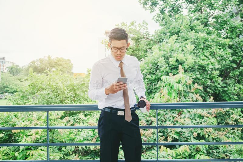 Businessman Using Mobile Phone Hand holding Coffee cup outdoor royalty free stock photo